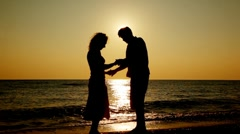 Boy and girl standing on beach, silhouettes at sunset, part2 Stock Footage
