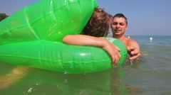 Father and daughter in Inflatable disc float at sea waves Stock Footage