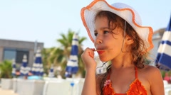 Girl licks stick from ice cream on beach Stock Footage