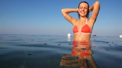 Girl stands waist-deep in sea Stock Footage