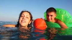 Girl and boy in inflatable disc is afraid, cannot swim, cling buoy into sea Stock Footage