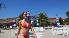 Girl goes behind camera at beach with downcast umbrellas and sunbeds Stock Footage