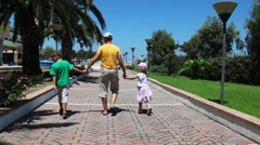 Man with daughter and son go on walkway to hotel Stock Footage