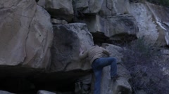 Man in Hat climbing up a cliff - stock footage
