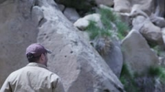 Man walking up to a cliff - stock footage