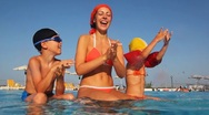 Mother with kids sit on pools section, clap their hands Stock Footage
