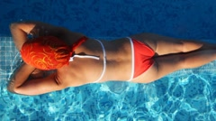 Woman lies on pools partition, below pool bottom with patches of light Stock Footage