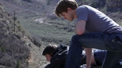 Two Teenagers Look Over The Edge Of A Cliff - stock footage