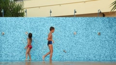 Stock Video Footage of Girl with boy run along wall for showers playfully turned on and off water