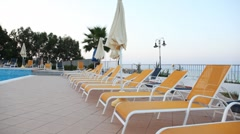 Beach beds and sunshades by pool Stock Footage
