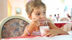 Little girl eats yogurt with spoon in plastic cup at table Stock Footage