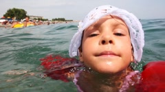 Little girl in inflatable arm ruffles swims at sea Stock Footage