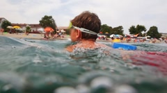 Boy swims in sea to shore, then camera shoots him under water Stock Footage