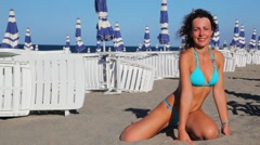 Woman poses kneeling on sand at beach Stock Footage