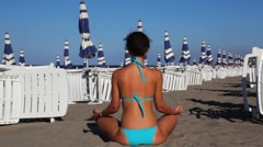 Woman meditates in lotus position on beach Stock Footage