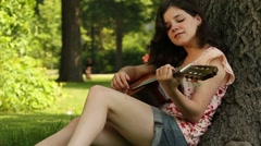 Teenager playing guitar in park Stock Footage