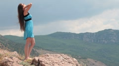 Young woman in mini dress on rock by the sea Stock Footage