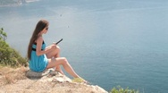 Stock Video Footage of woman reading e-book by the sea