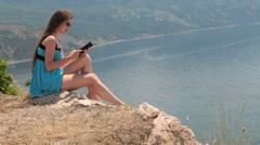 young woman in short blue dress reading the e-book - stock footage