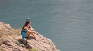 Young woman resting on the edge of  cliff by the sea Stock Footage
