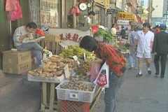Woman examines produce for sale in Chinatown Stock Footage