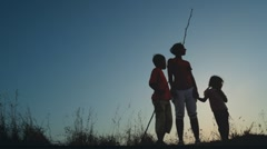 Mother and kids standing on hill, boy holding long thin stick Stock Footage