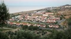View from hill of costal village, sea and hills has shown Stock Footage