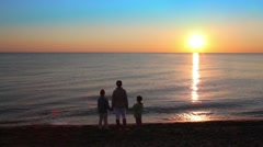 Mom and her two kids standing on beach Stock Footage