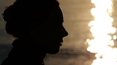 Silhouette of woman head with sunshine reflected in water Stock Footage