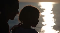 Silhouettes of mother and daughter heads with sunshine reflected in water behind Stock Footage