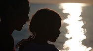 Stock Video Footage of Silhouettes of mother and daughter heads with sunshine reflected in water behind