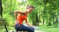 Young woman in the park with back pain, steadicam shot Stock Footage
