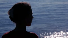 Silhouette of woman turned head with sun patterns on water behind Stock Footage