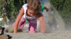 Two kids grabble by sand kicking up dust Stock Footage