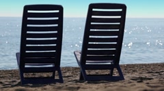 Two empty deckchairs stand on beach Stock Footage