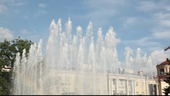 Tilt shot of the fountain with rainbow. Building on the background Stock Footage
