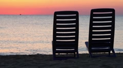 Two deckchairs stand on beach at evening Stock Footage
