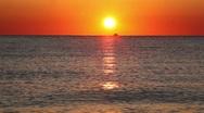 Fishing boat sails on horizon, sunset Stock Footage