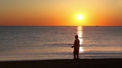 Man stands in sea water and fishing Stock Footage