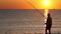 Man casts a fishing rod, and then beckoning fish - stock footage
