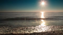 Surf washes part of the beach at sunset, sunshine reflect in water Stock Footage
