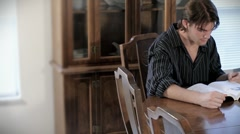 Young Man Sitting at Kitchen Table Studying Two Stock Footage