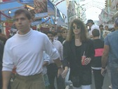 Walking with crowds of people through a street fair Stock Footage