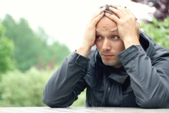 Sad man sitting by the table, outdoors, dolly shot NTSC - stock footage