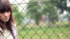 Sad woman behind chain-link fence, outdoors, dolly shot HD - stock footage