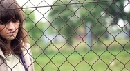 Stock Video Footage of Sad woman behind chain-link fence, outdoors, dolly shot HD