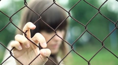 Sad woman behind chain-link fence, outdoors HD - stock footage