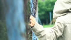 Woman in the hood walking by the chain-link fence, slow motion HD Stock Footage