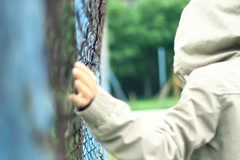 Woman in the hood walking by the chain-link fence, slow motion NTSC - stock footage