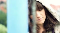 Sad beautiful woman by chain-link fence, outdoors, dolly shot HD - stock footage